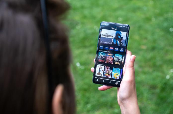 Una ragazza guarda uno smartphone su cui è installata Disney+