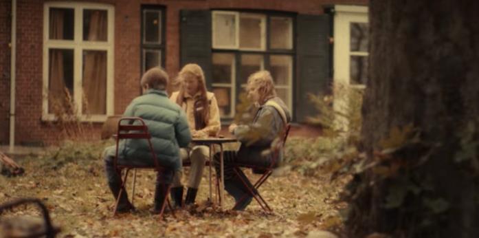 Tre bambini seduti a un tavolo all'aperto
