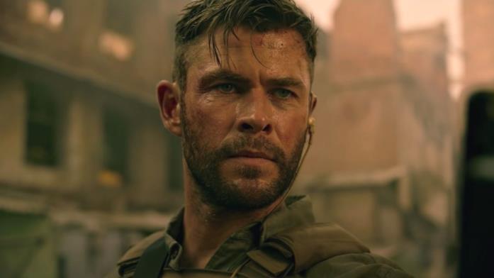 Primo piano di Chris Hemsworth sporco e sudato in una scena di Tyler Rake