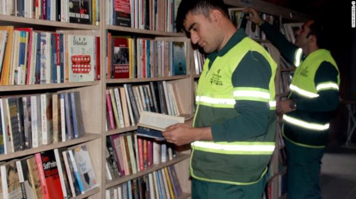 Primo piano di un netturbino mentre legge un libro nella biblioteca dei libri dimenticati di Ankara