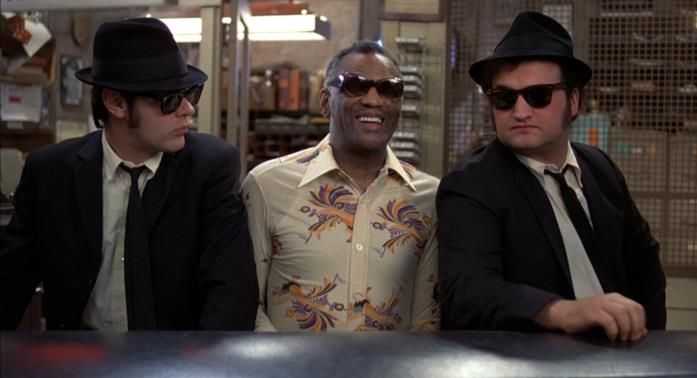 Una scena del film The Blues Brothers con i protagonisti seduti al pianoforte insieme a Ray Charles