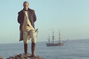 Il protagonista del film su uno scoglio, con la sua nave in lontananza