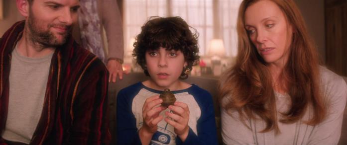 Adam Scott, Emjay Anthony e Toni Collette in una scena del film Krampus - Natale non è sempre Natale