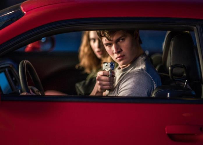 Baby e Deborah osservano fuori dal finestrino di una macchina rossa