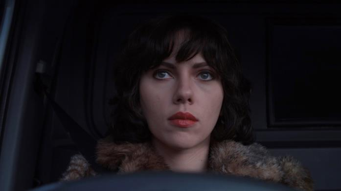 Un primo piano di Scarlett Johansson bruna e seduta in auto in una scena di Under the Skin