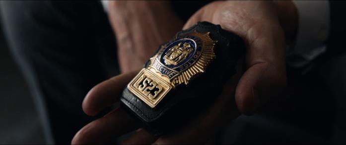 Michael mostra il distintivo da detective a Joanna