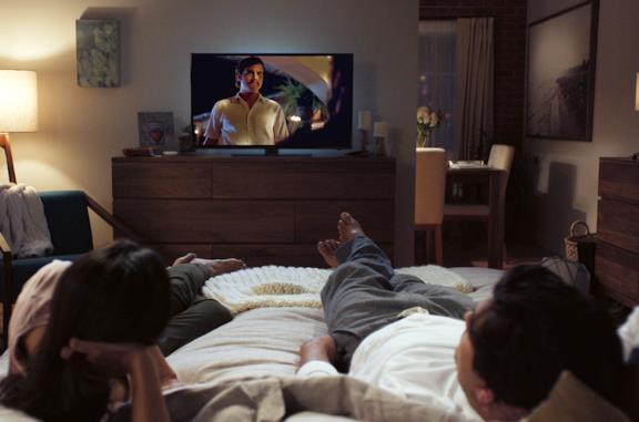 Una coppia sdraiata sul letto guarda la TV
