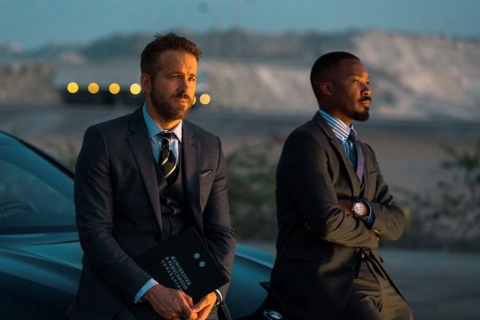 Ryan Reynolds e Corey Hawkins appoggiati su un'auto al tramonto in una scena di 6 Underground