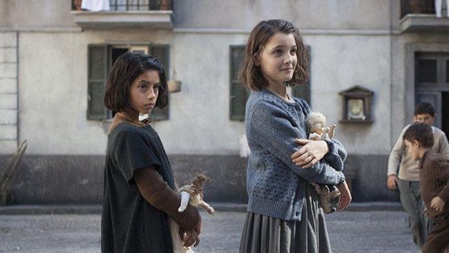 Lila e Lenù stringolo le loro bambole di pezza
