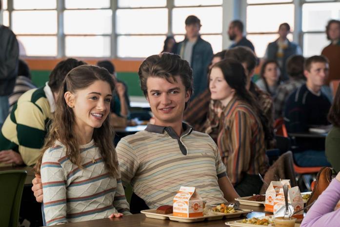 Steve e Nancy sorridenti e seduti a un tavolo nella mensa della scuola, con il vassoio del pranzo