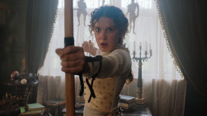 Enola Holmes stringe fra le mani un arco