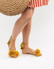 Sandali in pelle con fiore e cinturini con nappe