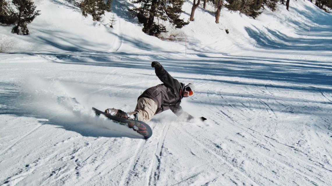 Sciatore con pantalone e giacca da snowboard