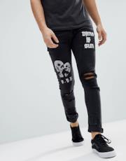 Jeans skinny nero slavato con strappi e stampe grunge