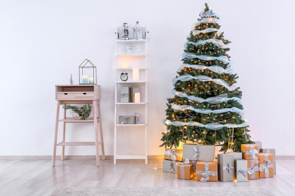 Albero di Natale decorato con nastri e lucine in salotto