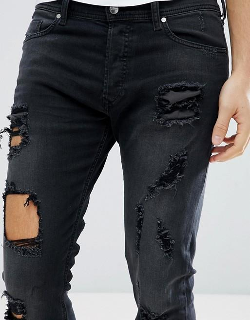 Dettaglio di jeans neri uomo strappati Diesel