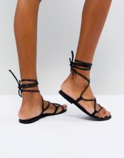 Sandali bassi in pelle con laccetti sulla gamba