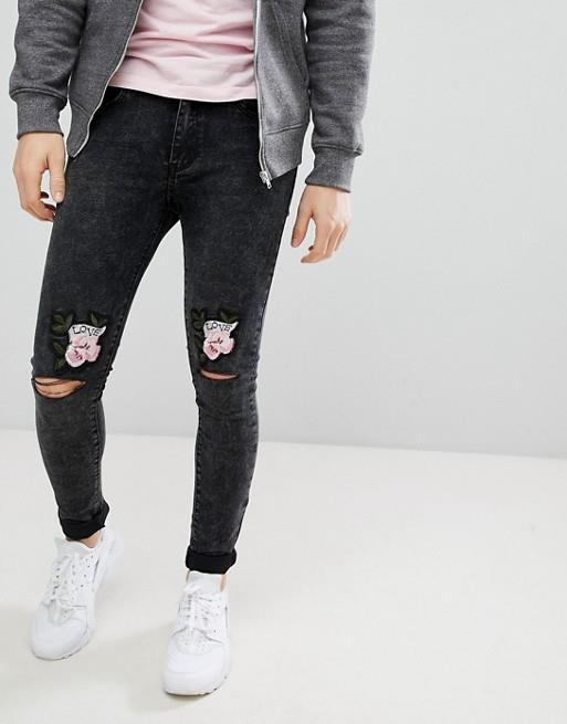 Jeans neri slavati da uomo con strappi e ricami