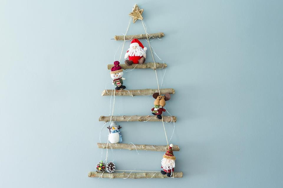 Albero di Natale stilizzato con personaggi natalizi appeso alla parete