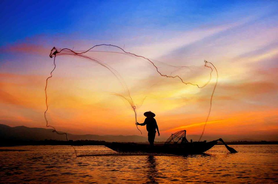 Cambodian man finishing with net at sunset