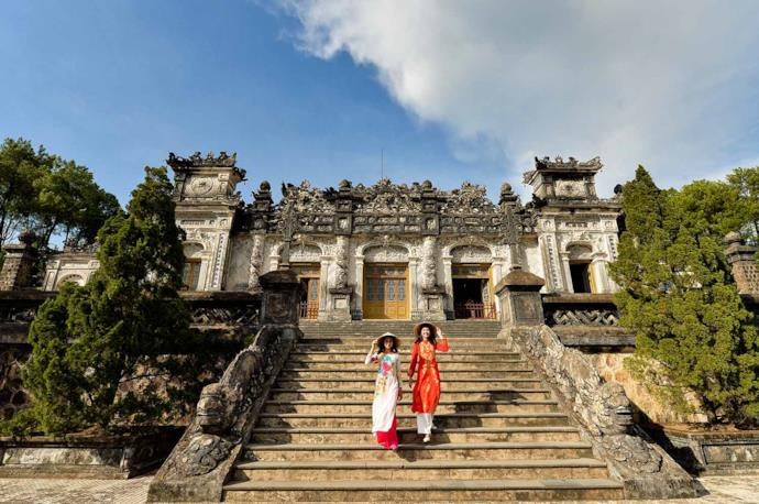 Two women walking down a monument in Hue