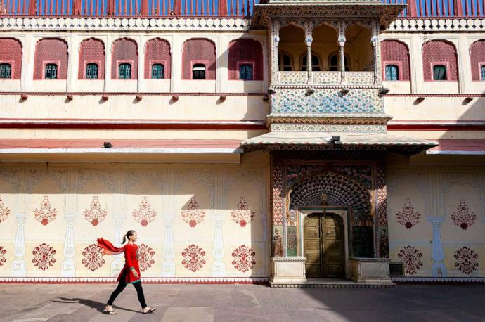 A woman walking in front of City palace of Jaipur