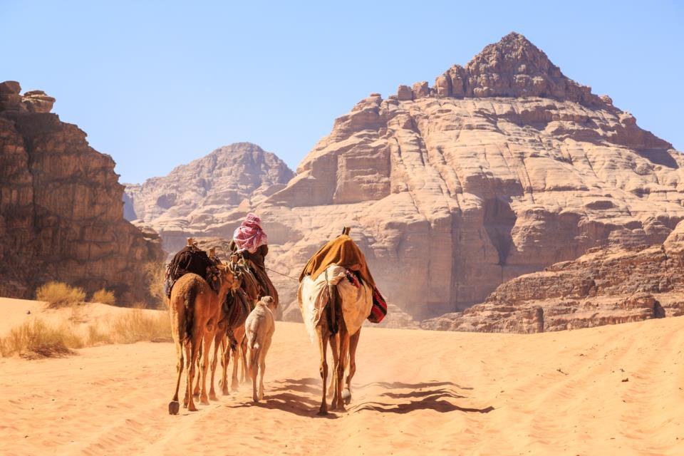 Men riding camels in Wadi Rum, Jordan