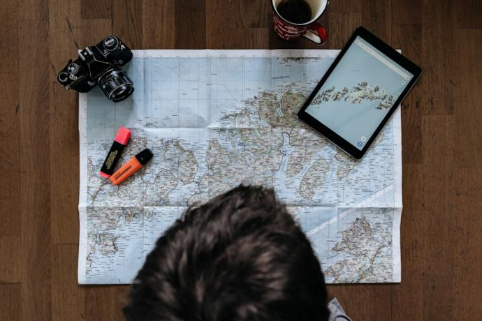 boy planning a vacation with a map