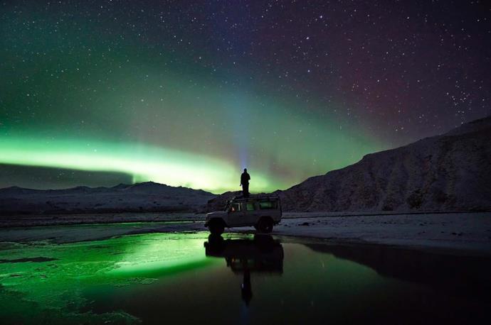 Turista guarda aurora boreale in auto in Islanda