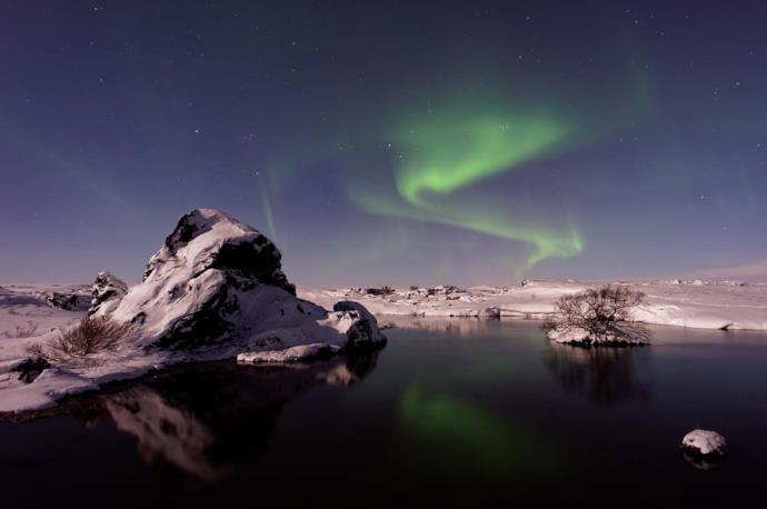 Aurora boreale su montagne innevate in Islanda