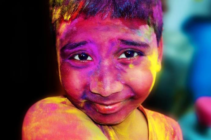 Bambino con viso ricoperto di polveri colorate per l'Holi Festival in India