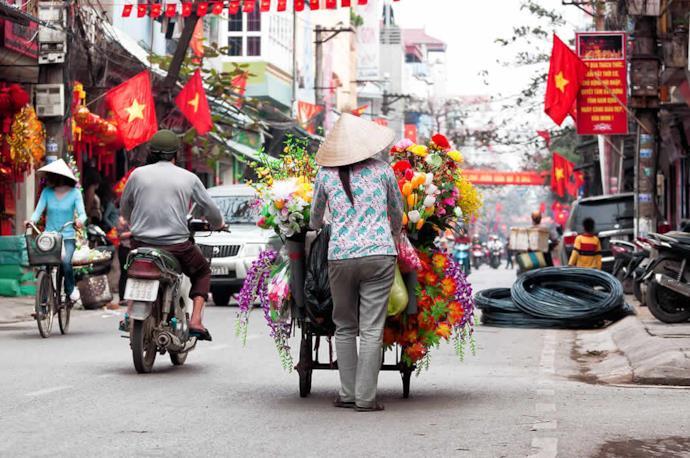 Donna vende fiori sulle strade di Hanoi, Vietnam