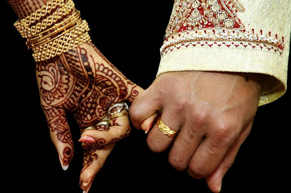 Coppia di giovani sposi indiani si tiene per mano